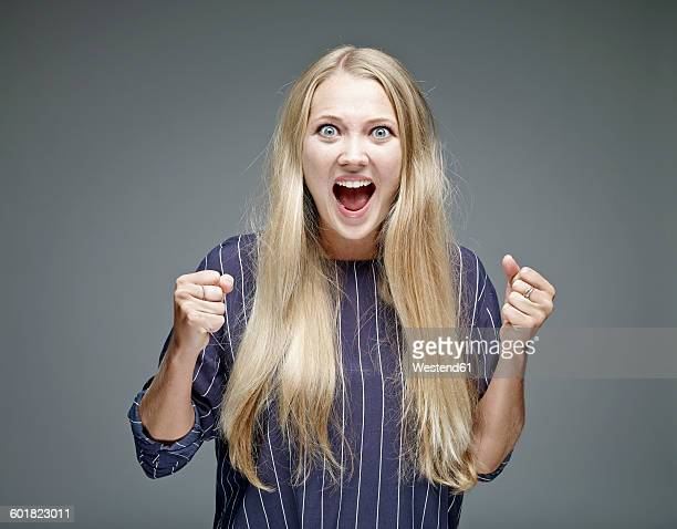 Portrait of excited young woman in front of grey background
