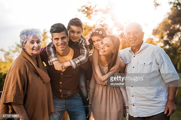 Portrait of extended family in nature at sunset.