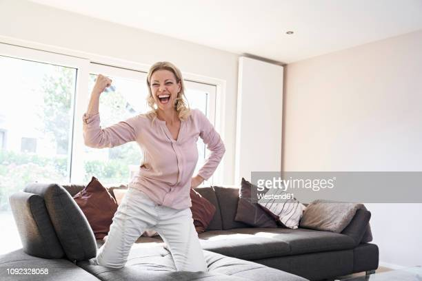 portrait of exuberant woman posing on couch at home - human arm stockfoto's en -beelden