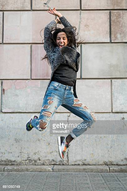 Portrait of exuberant young woman jumping around