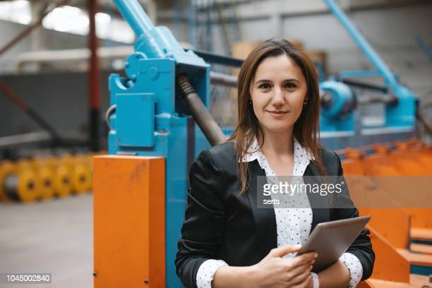 portrait of factory manager woman using tablet - metallic suit stock photos and pictures
