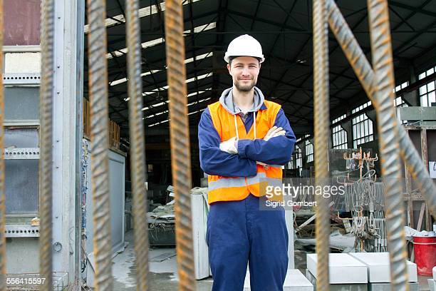 portrait of factory worker outside concrete reinforcement factory - sigrid gombert stockfoto's en -beelden