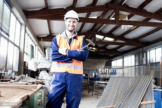 portrait of factory worker with hammer in concrete reinforcement factory - sigrid gombert stockfoto's en -beelden