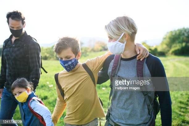 portrait of family and two children with face mask outdoors in spring nature, walking. - epidemic stock pictures, royalty-free photos & images
