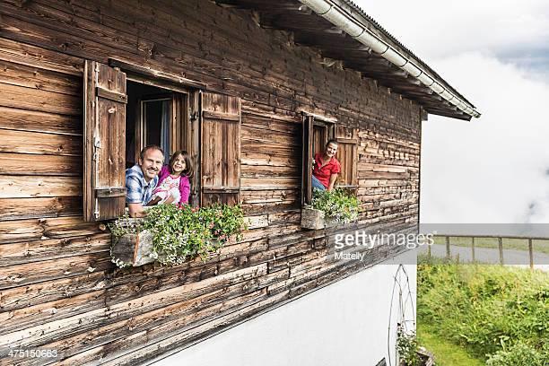 Portrait of family at chalet windows, Achenkirch,  Tyrol, Austria
