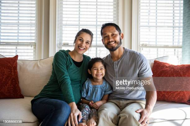 portrait of family at home on sofa - mortgage stock pictures, royalty-free photos & images
