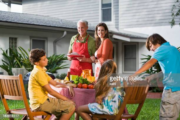 Portrait of family enjoying backyard barbecue