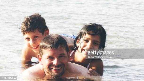 portrait of family enjoying in sea - sea swimming stock photos and pictures