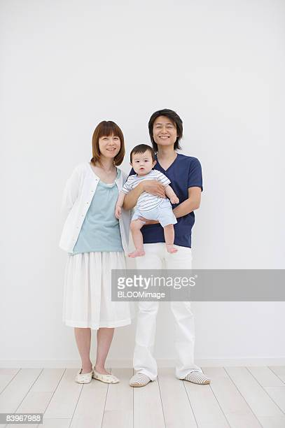 Portrait of family, father holding baby in arms