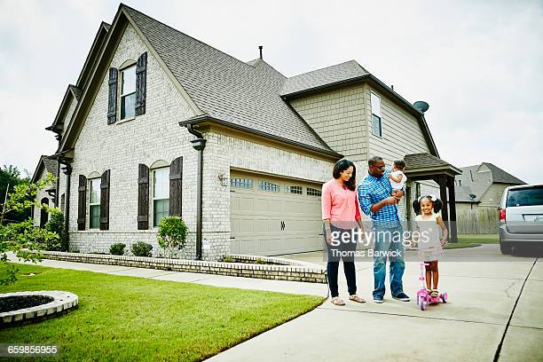 portrait of family in driveway in front of home - home ownership stock pictures, royalty-free photos & images