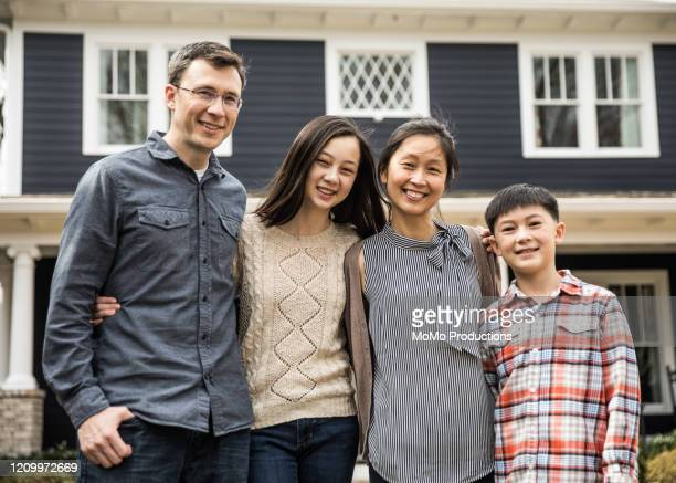 portrait of family in front of home - mixed race person stock pictures, royalty-free photos & images