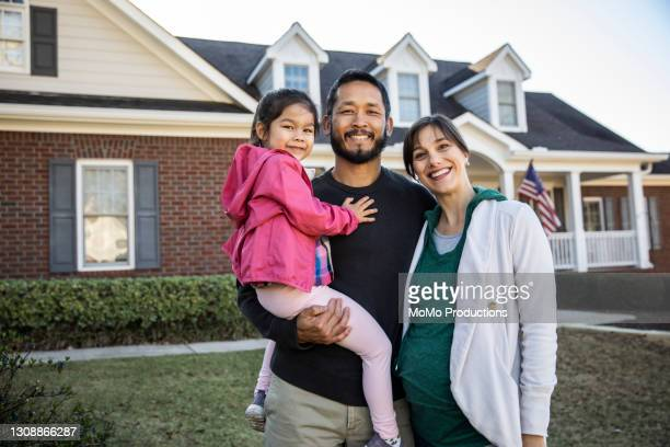 portrait of family in front of suburban home - mortgage stock pictures, royalty-free photos & images