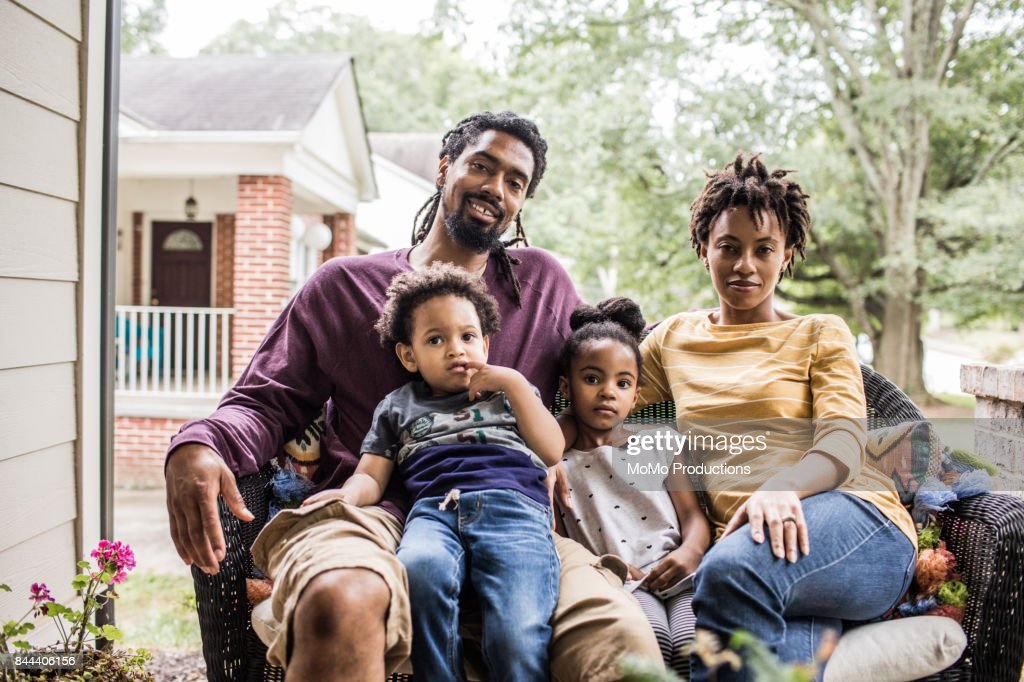 Portrait of family in front of suburban home : Stock Photo