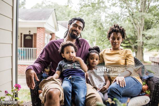 portrait of family in front of suburban home - four people stock pictures, royalty-free photos & images