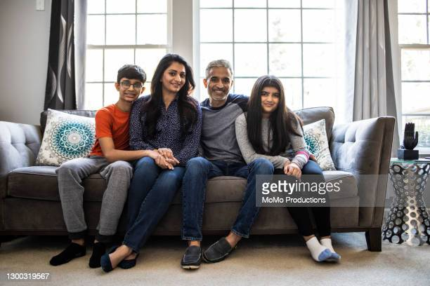 portrait of family in living room at home - sofa stock pictures, royalty-free photos & images