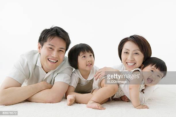 Portrait of family lying on floor, studio shot