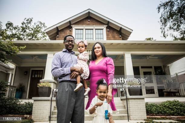 portrait of family outside of home - home insurance stock pictures, royalty-free photos & images