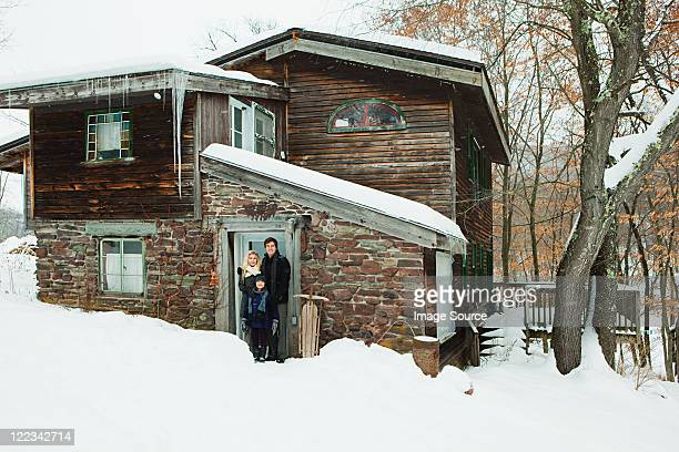 Portrait of family outside rustic house
