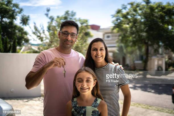 portrait of family showing new house key - mortgage stock pictures, royalty-free photos & images