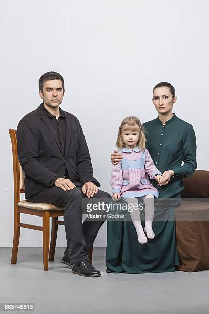 Portrait of family sitting against white background