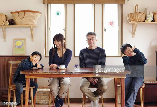 portrait of family sitting at dining table - 夫婦 ストックフォトと画像