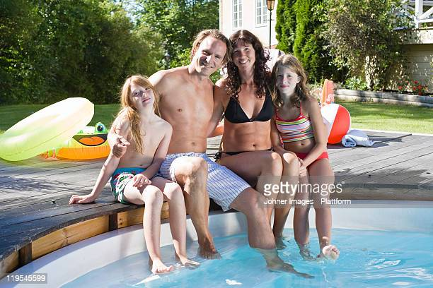 Portrait of family sitting at the edge of swimming pool