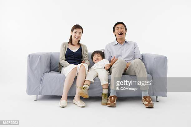 Portrait of family sitting on couch, smiling