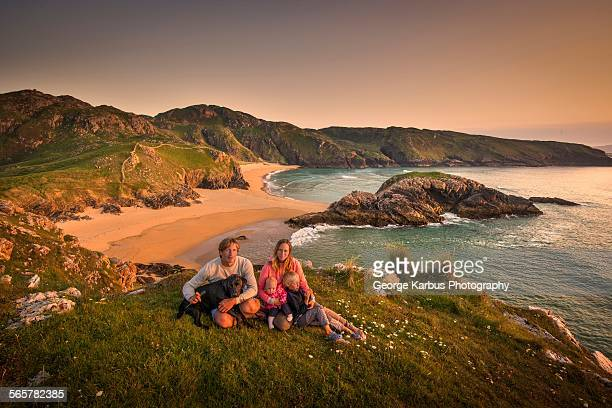 Portrait of family sitting on hillside, Murder hole beach, Melmor Head, Ireland