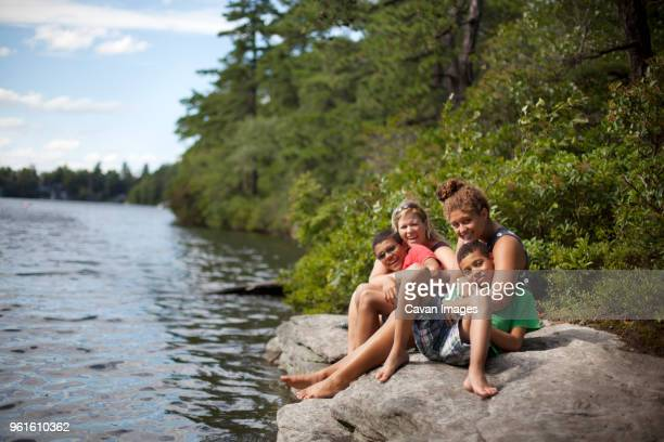Portrait of family sitting on rock by lake