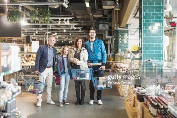 Portrait of family standing in organic food store
