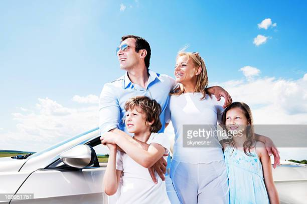 Portrait of family standing near Convertible car