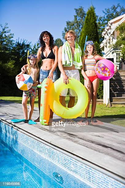 Portrait of family standing near swimming pool