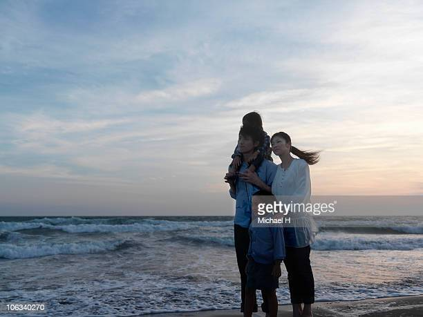 Portrait of family who stands in beach in evening