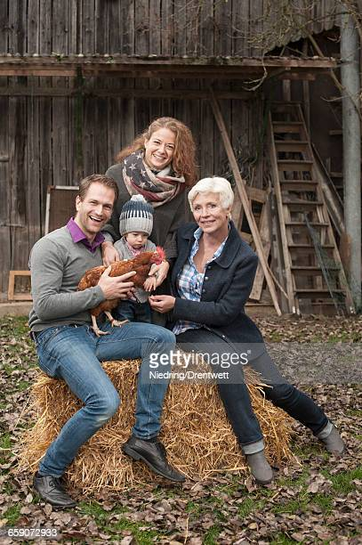 Portrait of family with chicken bird sitting in poultry farm, Bavaria, Germany