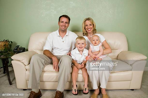 Portrait of family with daughter (9 months) and son (4 years) on sofa