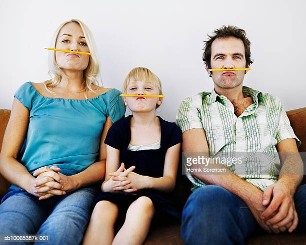 Portrait of family with daughter (6-7) posing with pencils under their noses