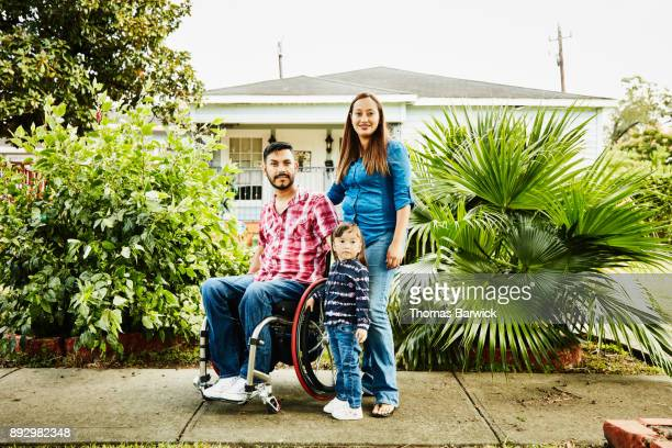 Portrait of family with father in wheelchair in front of home