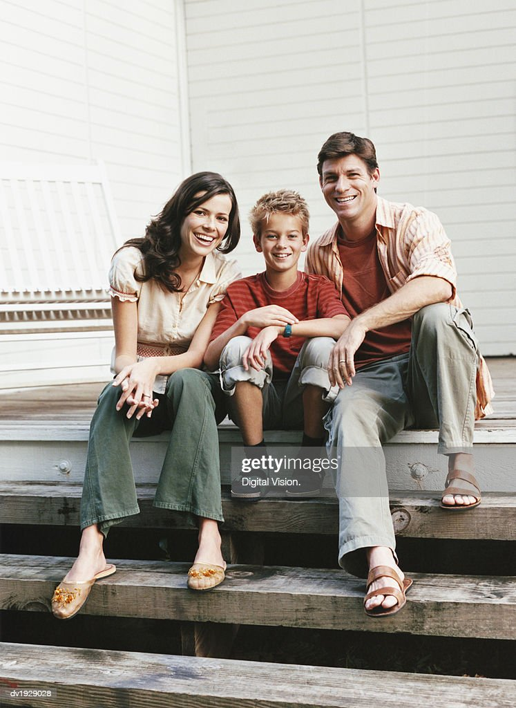 Portrait of Family With One Child Sitting on the Wooden Steps of Their Porch : Stock Photo