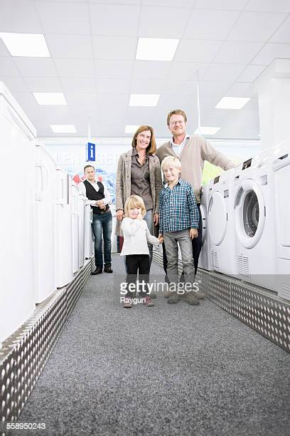 Portrait of family with two children browsing washing machines in electronics store