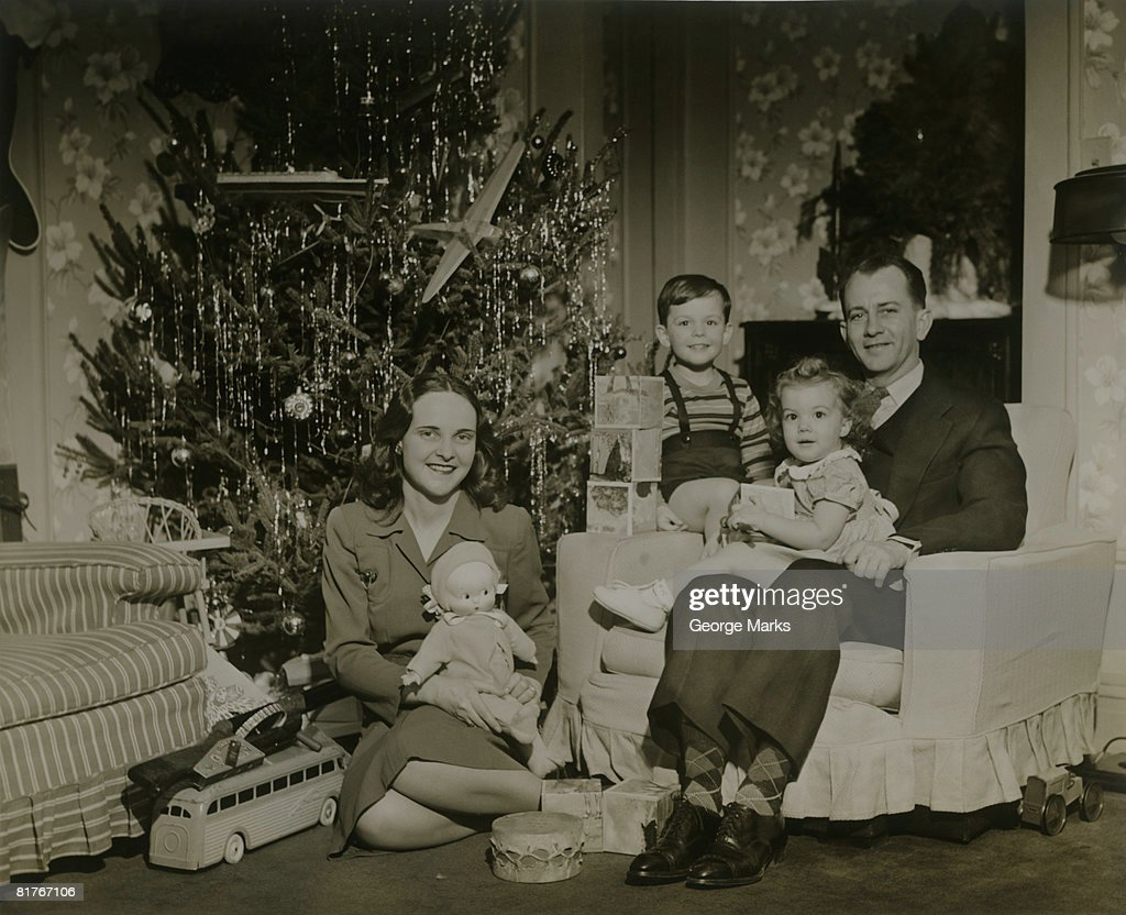 Portrait of family with two children (2-3 years) by Christmas tree in room : Stock Photo