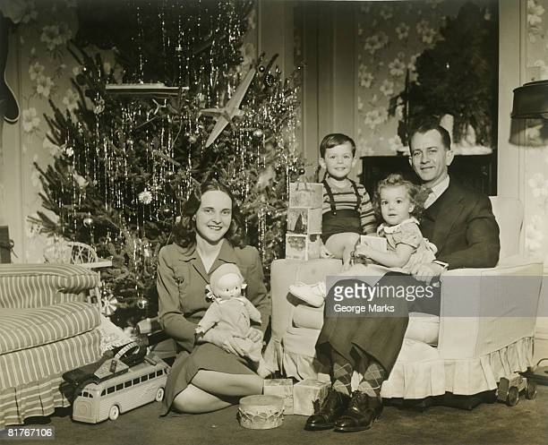 Portrait of family with two children (2-3 years) by Christmas tree in room
