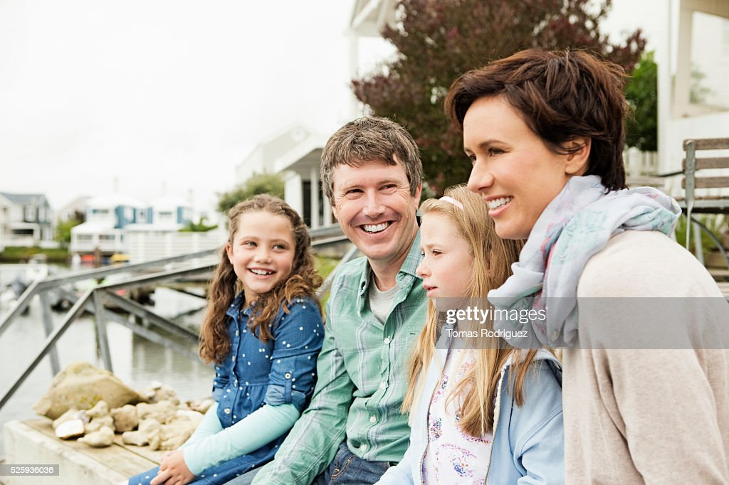 Portrait of family with two girls (6-7), (8-9) relaxing by water : Stock Photo