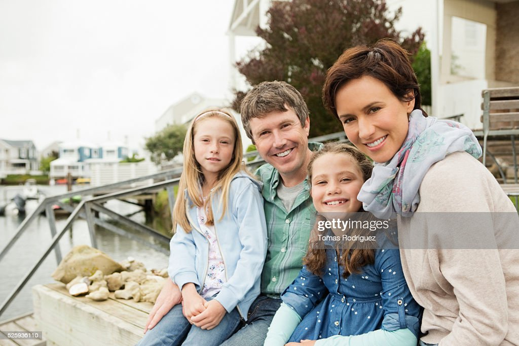 Portrait of family with two girls (6-7), (8-9) relaxing by water : Foto de stock