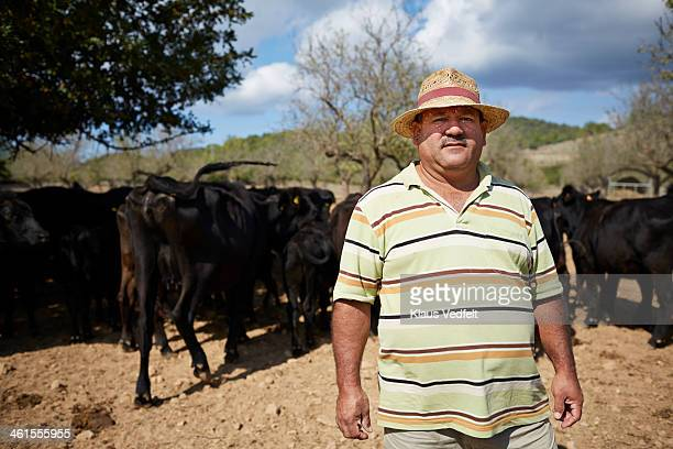 Portrait of farm worker in front of Angus cattle