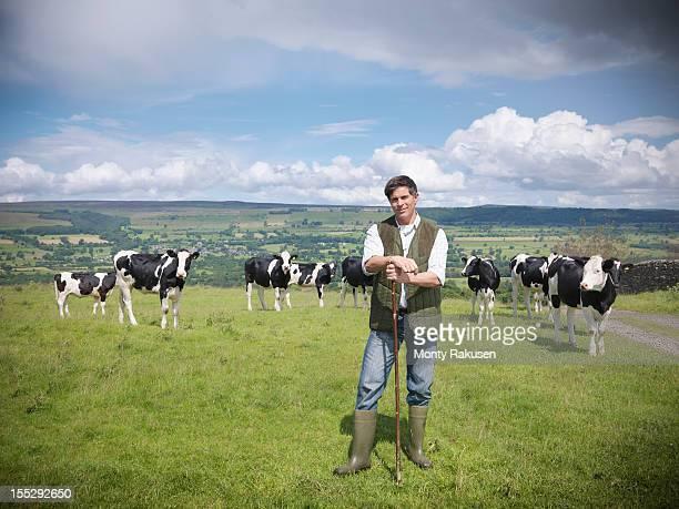 portrait of farmer and cows in field - agricultor imagens e fotografias de stock