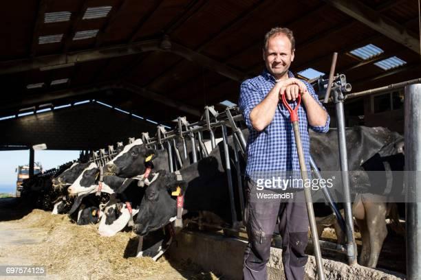 Portrait of farmer holding a shovel on a cow farm