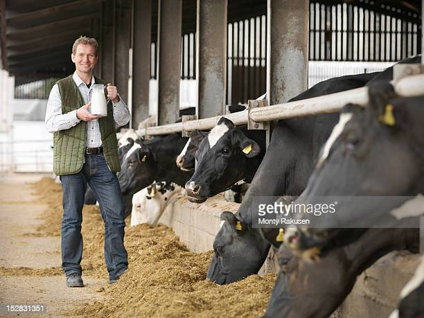 Portrait of farmer holding jug of milk with cows feeding in dairy shed