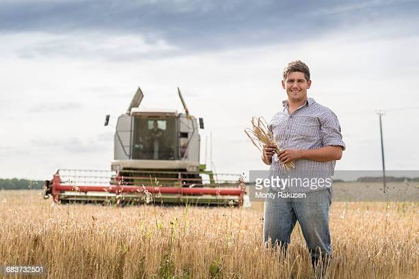 Portrait of farmer holding sheaf of organic barley in field