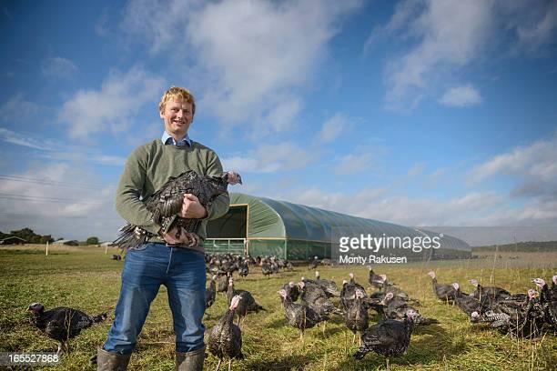 Portrait of farmer holding turkey on free range turkey farm with farm building in background