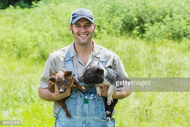 Retrato de agricultor sostiene dos cochinillos